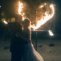 couple kissing in front of heart of fire