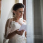 bride is reading a letter by the window