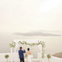 elopement-couple-drinking-champagne-and-enjoy-the-view-of-Santorini-caldera-in-santa-irene